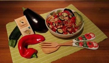 Erfrischender Salat mit Mozzarella in einer Schüssel mit Paprika, Zucchini, Melanzani, Holzbesteck und Naturala Vegibuster Gewürzmischung