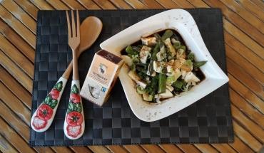 Grüner Spargelsalat mit Mozzarella auf einem Teller angerichtet mit Holzbesteck