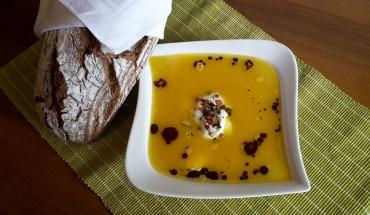 Kürbiscremesuppe nach bäuerlicher Art angerichtet auf einem Teller mit einem Laib Brot