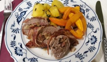 Mit Kastanien gefülltes Schweinsfilet mit Kürbisspalten und Kartoffeln auf einem Teller