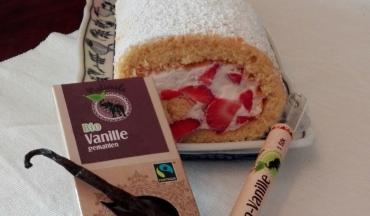 Vanillebiscuit mit Erdbeerfüllung auf einem Teller mit einer Packung Naturala Vanille gemahlen und einer Bourbon-Vanilleschote von Naturala
